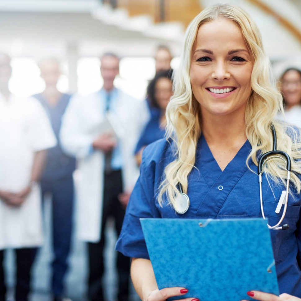 Cheerful blond medic with documents in hospital